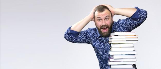 Student volwassen baard man met stapel boek in een bibliotheek
