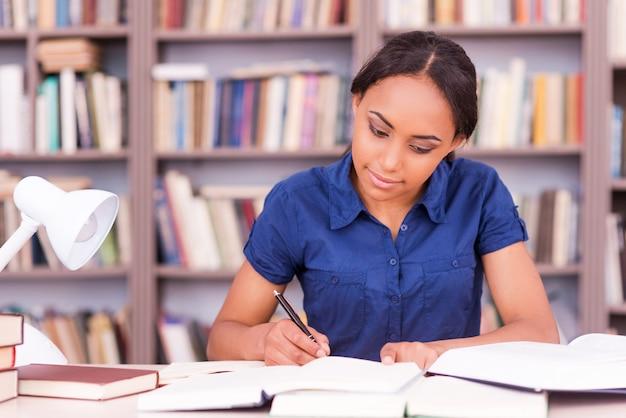 Student voorbereiden op de examens. zelfverzekerde jonge zwarte vrouw die iets in haar notitieblok schrijft en een boek leest terwijl ze aan de bibliotheekbalie zit