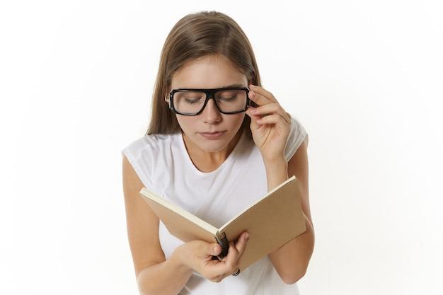 Student vrouw bril dragen voor een goede visie, leerboek in handen houden