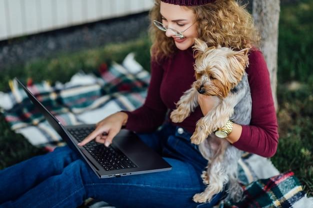 Student vrouw zittend op de deken en hebben een picknick tijd met haar yorkshire terriër hond. kijk naar de laptop.