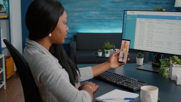 Student zit aan bureau in woonkamer met online videogesprek teleconferentievergadering met behulp van telefoonwebcam