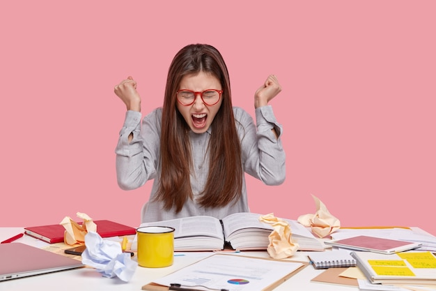 Student zit aan bureau met documenten