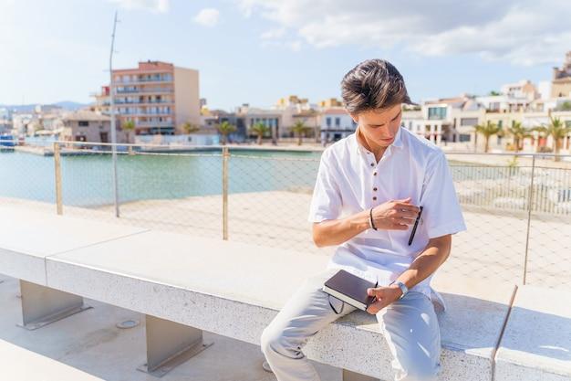 Student zit op een bankje en haalt een pen uit een zak