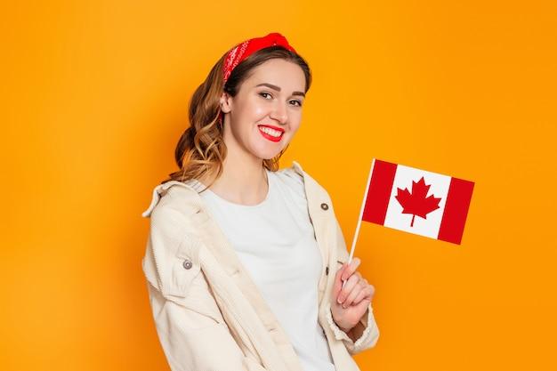 Studente die en een kleine vlag van canada glimlacht houdt die over oranje achtergrond wordt geïsoleerd