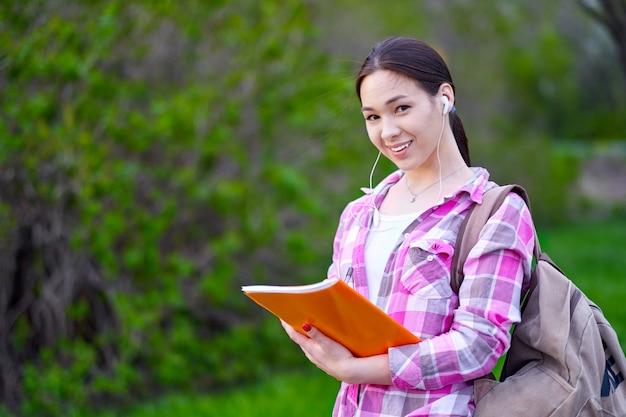 Studente die en een stapel omslagen in de zomerpark glimlachen houden