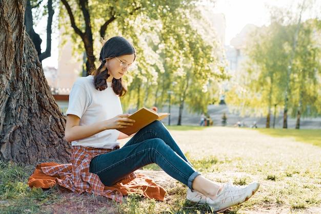 Studente die in glazen boek in het park lezen