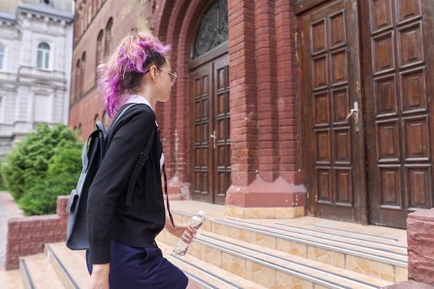 Studente die naar school gaat, tiener in uniform met rugzak op de trappen van het schoolgebouw. terug naar school, terug naar het concept van het universiteitsonderwijs