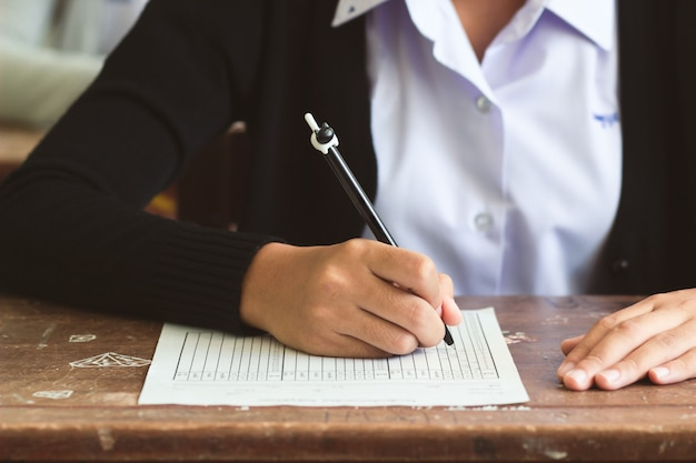 Studente die van het meisje en het schrijven examen glimlacht