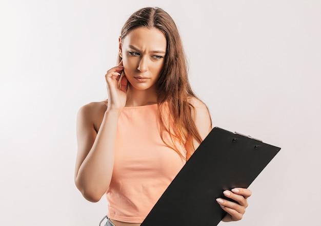 Studente fronst ongenoegen en leest informatie in documenten. mooie jonge zakenvrouw houdt een klembord met mockup op grijze achtergrond. studie en bedrijfsconcept. online leren
