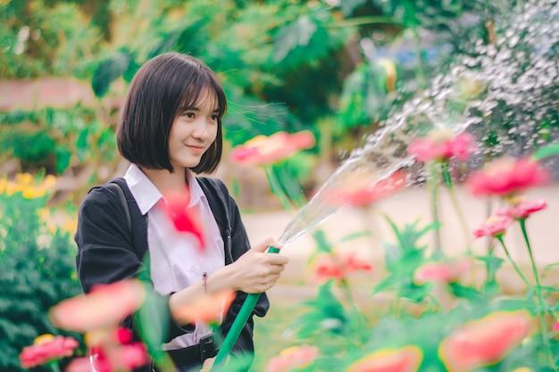 Studente het water geven bloem in de tuin