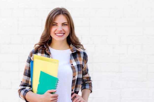 Studente houdt mappen en een notitieboekje in haar handen en glimlacht