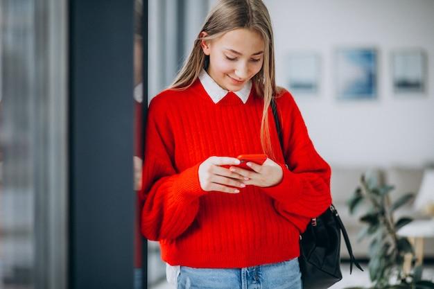 Studente in rode sweater die telefoon met behulp van