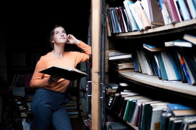 Studente leest een boek in de oude bibliotheek een vrouw zoekt informatie in de archieven