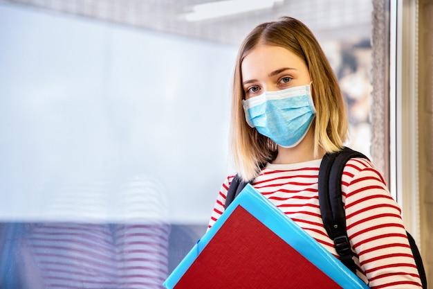 Studente met beschermend medisch masker. portret van blonde vrouwelijke student in de buurt van raam aan de universiteit tijdens coronavirus covid lockdown met kopieerruimte.