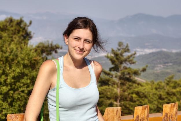 Studente op vakantie, poseren voor de fotograaf tegen de achtergrond van een berglandschap.