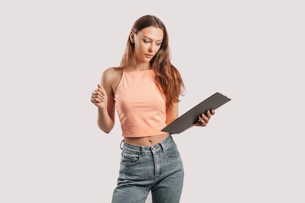 Studente schrijft informatie. mooie jonge zakenvrouw geïsoleerd op een grijze achtergrond. het bereiken van het bedrijfsconcept van de carrièrerijkdom. mockup kopie ruimte. houd een klembord met documenten vast
