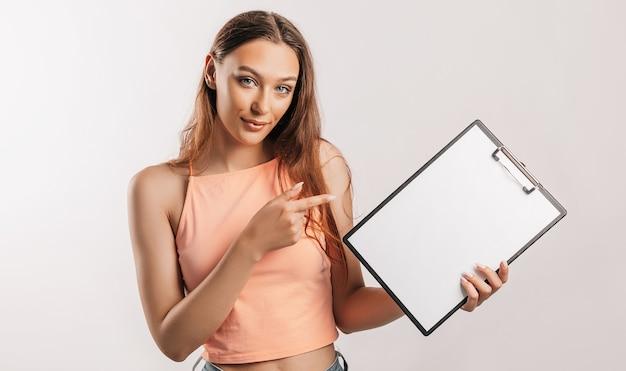 Studente wijst naar het blad. mooie jonge zakenvrouw houdt een klembord met mockup lege ruimte geïsoleerd op een grijze achtergrond. studie en bedrijfsconcept. cover voor online leren