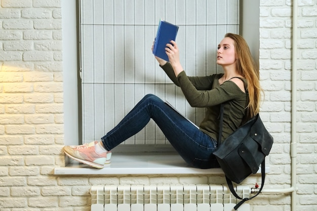 Studente zittend op de vensterbank, studeren, notebook lezen. jonge mooie vrouw met rugzak universiteitsstudent, onderwijs, zelfstudie