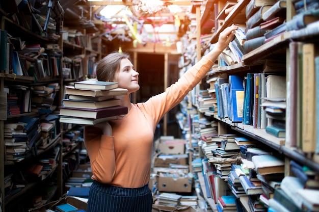 Studente zoekt literatuur in de oude bibliotheek, neemt een boek uit de boekenkast, een vrouw zoekt informatie in de archieven