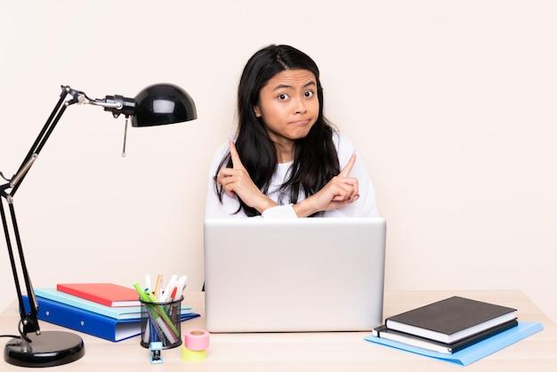 Studenten aziatisch meisje in een werkplaats met laptop die op beige achtergrond wordt geïsoleerd die aan de lateralen richten die twijfels hebben