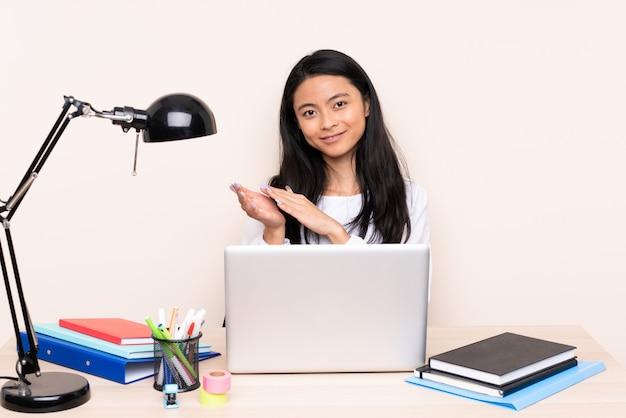 Studenten aziatisch meisje in een werkplaats met laptop die op beige achtergrond wordt geïsoleerd die na presentatie in een conferentie toejuichen
