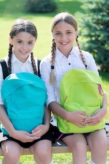 Studenten buiten in het zomerpark glimlachend gelukkig. meisjes met schooltassen. kind met rugzak. vrolijke tijd. mode kleine meisjes met rugzak in park. kinderen met rugzak glimlachen.