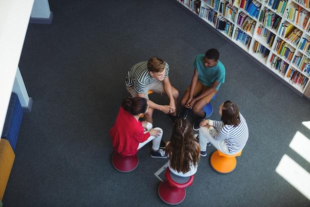 Studenten communiceren met elkaar in bibliotheek
