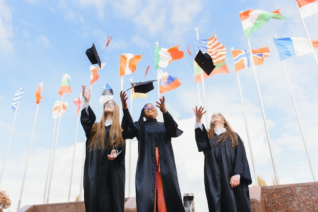 Studenten die afstudeerhoeden in de lucht gooien vieren