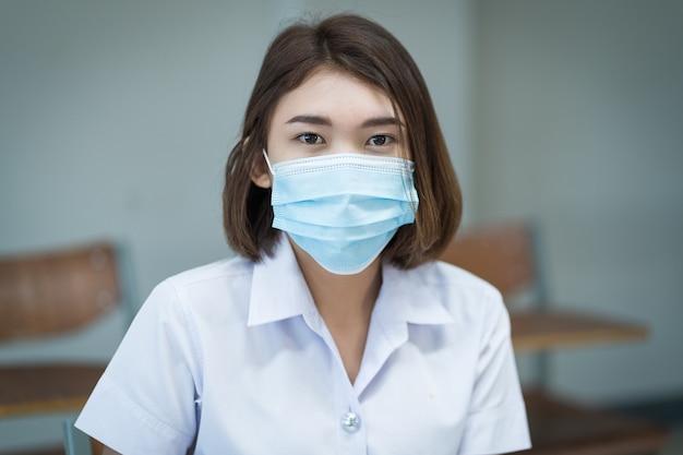 Studenten die beschermende maskers dragen in de klas