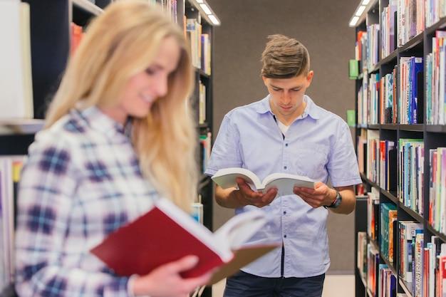 Studenten die boeken lezen tussen boekenplanken