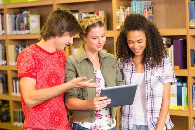 Studenten die digitale tablet in bibliotheek gebruiken