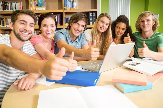 Studenten die duimen omhoog in bibliotheek gesturing