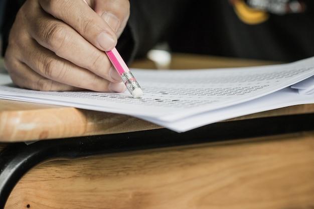 Studenten die een potloodwisser vasthouden tijdens het afleggen van examens, onderzoeksruimte, optische antwoordformulier schrijven in de klas van de middelbare school, zicht op het hebben van een test in de klas op stoelrijen, onderwijsgeletterdheidsconcept.