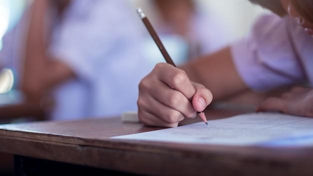 Studenten die examen met spanning in schoolklaslokaal nemen.
