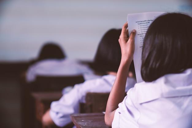 Studenten die examen met spanning in schoolklaslokaal nemen