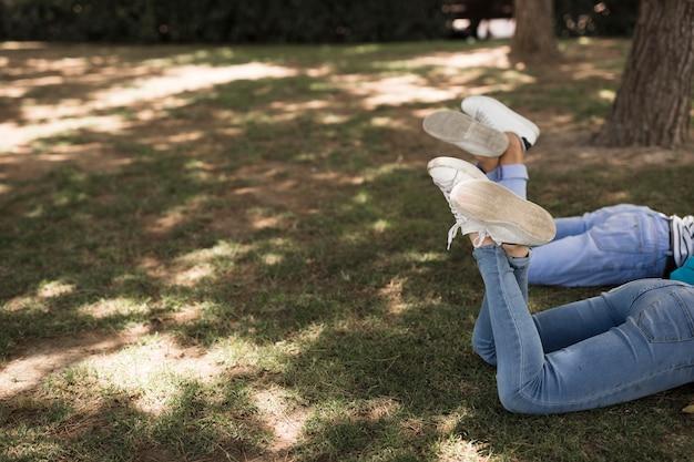 Studenten die in park met gekruiste benen liggen