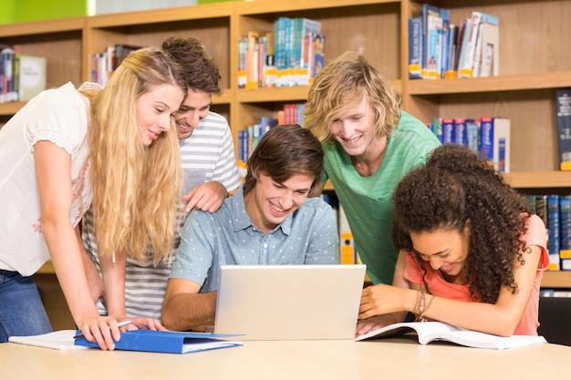 Studenten die laptop in bibliotheek met behulp van