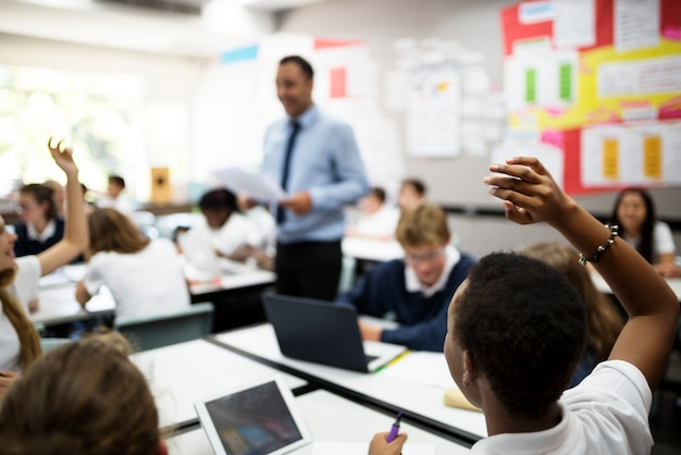Studenten die met hun handen reageren op hun leraar