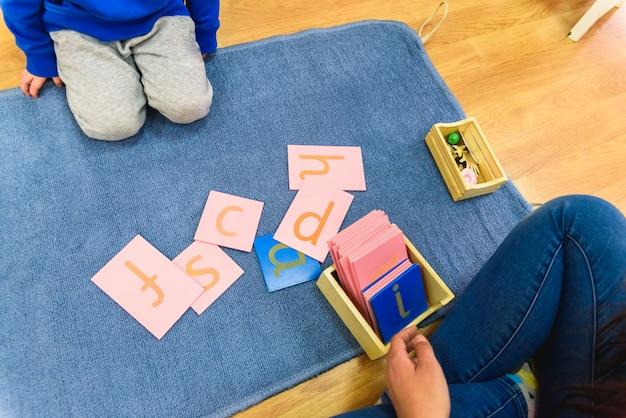 Studenten die montessori-materiaal verwerken in een school op een mat tijdens een les.