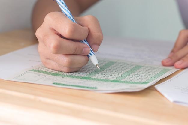 Studenten die potlood in handen houden die examens nemen