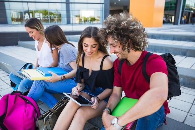 Studenten die tablet gebruiken dichtbij vrienden