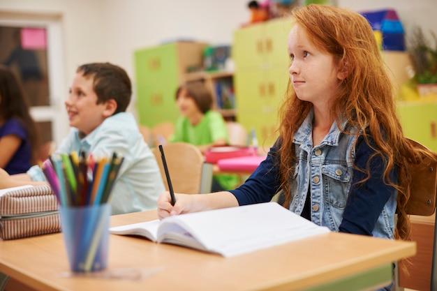Studenten die tijdens de les aan haar bureau zitten,