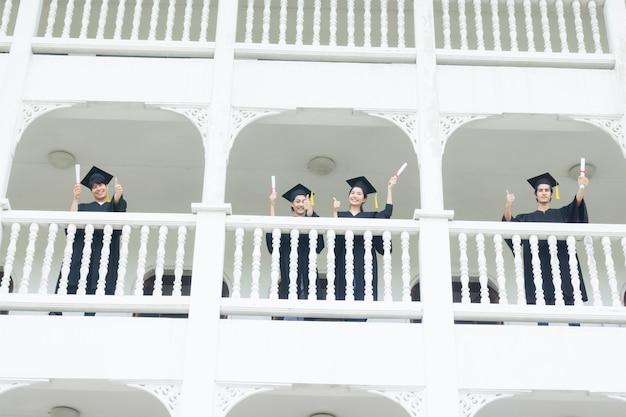 Studenten die zich gelukkig voelen met afstudeerjurken staan bij het ganggebouw.