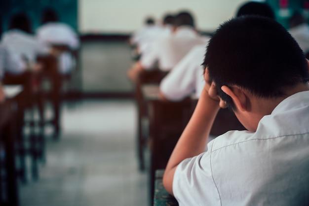 Studenten doen examen antwoordbladen oefeningen in de klas van de school met stress.