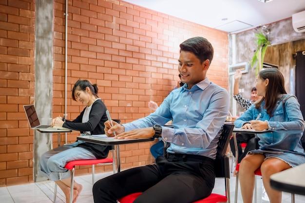 Studenten doen examens om cijfers te verzamelen aan het einde van het semester en er is een jonge leraar die toezicht houdt op de examens in de klas.