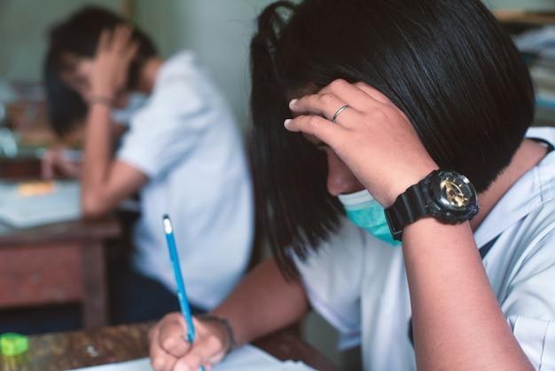 Studenten dragen een masker om corona-virus of covid-19 te beschermen en doen oefeningen met examenantwoordbladen in de klas van school met stress.