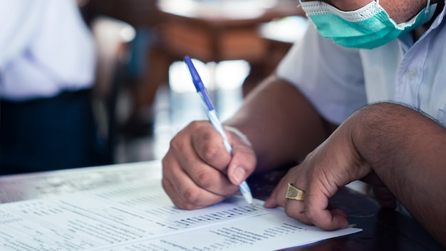 Studenten dragen masker ter bescherming van covid-19 en doen examen in de klas met stress