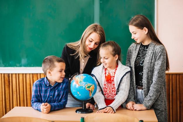 Studenten en schoolleraar kijken naar globe