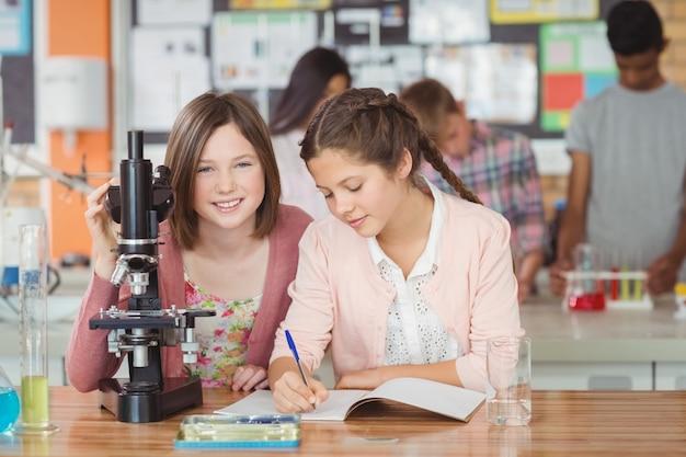 Studenten experimenteren op microscoop in laboratorium