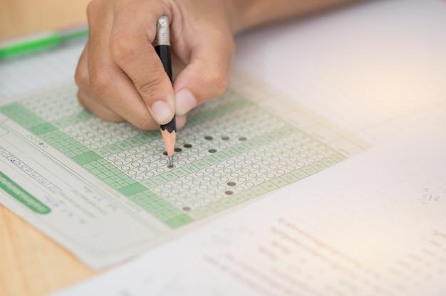 Studenten hand testen examen doen met potlood tekening geselecteerde keuze